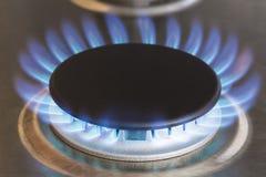 Close-up van blauwe vlammen van aardgas kokend element op keukenfornuis stock fotografie