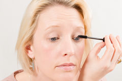 Close-up van Blonde Dame Applying Mascara Make-Up stock afbeeldingen
