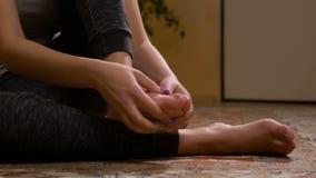 Close-up van blootvoetse jonge vrouw die haar verstuikte voet masseren die pijnlijke symptomen hebben stock video