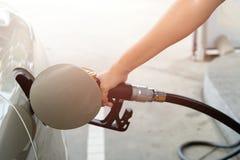 Close-up van brandstof van de mensen de pompende benzine in auto bij benzinestation brandstof stock afbeeldingen