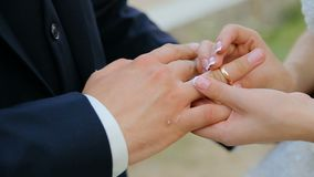 Close-up van bruid en bruidegom die trouwringen over groene aardachtergrond ruilen stock footage