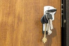 Close-up van bundel van verschillende sleutels in zeer belangrijk gat in houten textu Stock Afbeeldingen