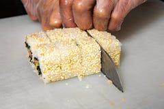 Close-up van chef-kokhanden die sushibesnoeiingen oprollen in gedeelten op keuken royalty-vrije stock afbeeldingen