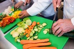Close-up van chef-koks die groenten hakken Stock Fotografie