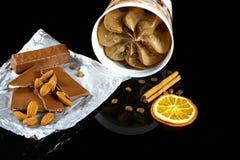 Close-up van chocoladeroomijs, melkchocola en amandelen, koffiebonen, stok van kaneel en een plak van droge geïsoleerde sinaasapp Stock Fotografie
