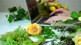 Close-up van computer en bloemenmeisjes` s hand wordt geschoten die de drukken op gadget binnen op lijst onder installaties in bu stock video