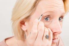 Close-up van Dame Plucking Eyebrows stock foto