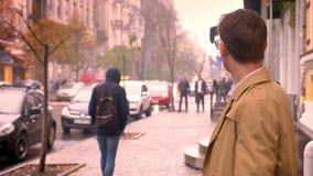 Close-up van de aantrekkelijke Kaukasische mens die het horloge controleren en rond wachten op kijken gestoord en betroffen in de stock footage
