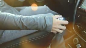 Close-up van de actie Het meisje in de auto zet het toestel aan en wordt aan de gang terwijl het duwen van de pedalen Het concept stock videobeelden
