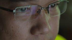 Close-up van de Aziatische mens met sociale media die in zijn glaslenzen nadenken stock footage