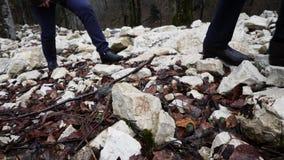 Close-up van de benen die van mensen op stenen beklimmen Twee mensen beklimmen steenhelling van berg met gevallen bladeren in de  stock videobeelden