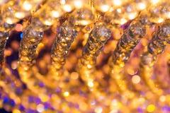 Close-up van de decoratie van de kristalkroonluchter met gouden licht wordt geschoten dat Royalty-vrije Stock Afbeeldingen