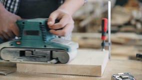 Close-up van de elektrische oppoetsende schuurmachine die van de machineriem met hout in workshop werken stock video