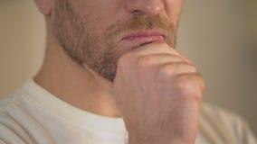 Close-up van de ernstige jonge mens met baard die kin wrijven, die twijfels, het denken hebben stock videobeelden