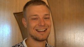 Close-up van de glimlachende jonge mens die die camera bekijken op witte achtergrond wordt geïsoleerd Portret van een kerel met b stock footage