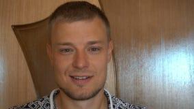 Close-up van de glimlachende jonge mens die die camera bekijken op witte achtergrond wordt geïsoleerd Portret van een kerel met b stock video
