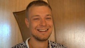 Close-up van de glimlachende jonge mens die die camera bekijken op witte achtergrond wordt geïsoleerd Portret van een kerel met b stock videobeelden