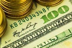 Close-up van de gouden muntstukken op honderd dollarsbankbiljet Royalty-vrije Stock Foto's