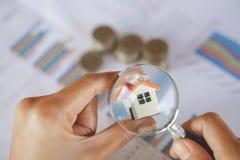 Close-up van de Hand die van een Businessperson Huis Modelthrough magnifying glass die, Huis bekijken concept met het overdrijven royalty-vrije stock afbeelding
