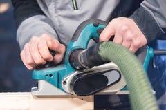 Close-up van de hand die van een timmerman met een elektrisch vliegtuig met zuiging die van zaagsel werken en houten bars nivelle stock foto