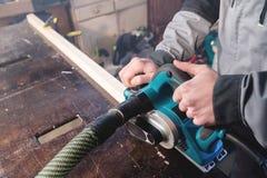 Close-up van de hand die van een timmerman met een elektrisch vliegtuig met zuiging die van zaagsel werken en houten bars nivelle stock fotografie