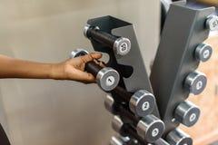 Close-up van de hand die van de sterke vrouw zware domoor in gymnastiek nemen Royalty-vrije Stock Afbeeldingen