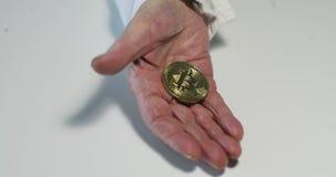 Close-up van de hand van de oude vrouw met diepe rimpels die de Gouden muntstukken van Bitcoin tonen BTC stock video