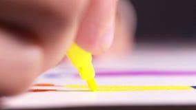 Close-up van de hand van de vrouw met gele gevoelde pen die één of ander cijfer trekt op het document blad bij de lijst actie cre stock videobeelden