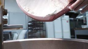 Close-up van de handen die van de bakker bloem gieten in een professionele knedermachine in keuken van bakkerij Voorraadlengte de stock foto