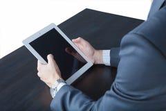 Close-up van de handen die van een zakenman tabletzitting houden bij een geïsoleerde lijst Stock Afbeelding