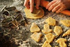 Close-up van de handen die van de vrouw met deeg werken en koekjes maken stock fotografie