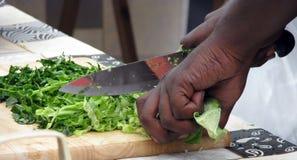 Close-up van de handen die van vrouwen groenten hakken stock foto's