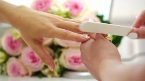 Close-up van de handen van een manicure die de spijkers van een jonge vrouw indienen stock videobeelden
