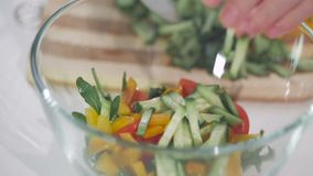 Close-up van de handen van een vrouw die ingrediënten voor plantaardige salades in een glaskom vouwen stock videobeelden