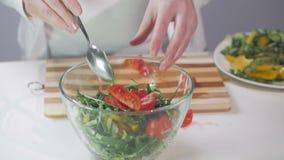Close-up van de handen van een vrouw die ingrediënten voor plantaardige salades in een glaskom vouwen stock footage