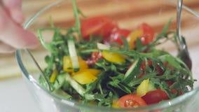 Close-up van de handen van een vrouw die ingrediënten voor plantaardige salades in een glaskom vouwen stock video