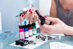 Close-up van de handen van een vrouwelijke kunstenaar die een professionele tatoegeringsmachine voorbereiden stock fotografie