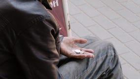 Close-up van de handen van de stadsbedelaars In zijn hand zijn zichtbare muntstukken die hij erin slaagde om te verzamelen Social stock video