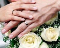 Close-up van de holdingshanden van het jonggehuwdepaar Stock Afbeelding
