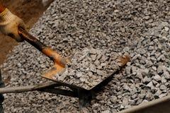 Close-up van de holdingsschop van de mensenhand en natuurlijke zwarte houtskool voor achtergrond wordt geschoten die Beeldidee ov stock foto