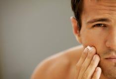 Close-up van de jonge mens die scheercrème toepast stock foto