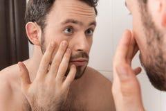 Close-up van de jonge mens die zijn oog in spiegel onderzoeken Royalty-vrije Stock Afbeelding