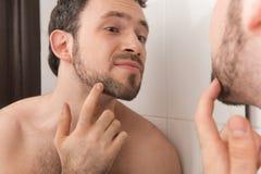 Close-up van de jonge mens die zijn stoppelveld in spiegel onderzoeken Stock Foto