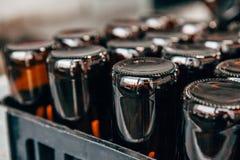 Close-up van de lege bovenkant van bierflessen - neer in een plastic doos stock foto's