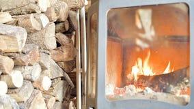 Close-up van in de loop van de dag het branden van brandhout in een eigengemaakt modern fornuis achter vuurvast glas naast een gr stock video