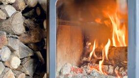 Close-up van in de loop van de dag het branden van brandhout in een eigengemaakt modern fornuis achter vuurvast glas naast een gr stock footage