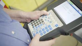 Close-up van de machinecontrolebord van de arbeidersholding in fabriek actie De handen die van mensen moderne multi-knoopcontrole stock videobeelden