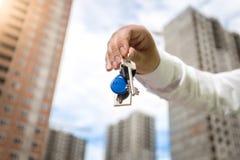 Close-up van de mannelijke sleutels van de handholding van nieuw huis op achtergrond van Stock Foto