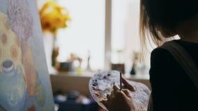 Close-up van de mengelingsverven van de vrouwenkunstenaar met borstel in palet en alvorens stillevenbeeld op canvas in kunststudi stock videobeelden