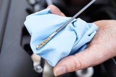 Close-up van de Mens die het Niveau van de Motor van een autoolie controleren op Peilstok stock foto